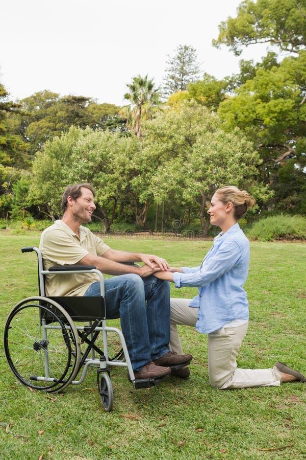 Lächelnder Mann Im Rollstuhl Mit Dem Partner, Der Neben Ihm Knit Lizenzfreies Stockbild