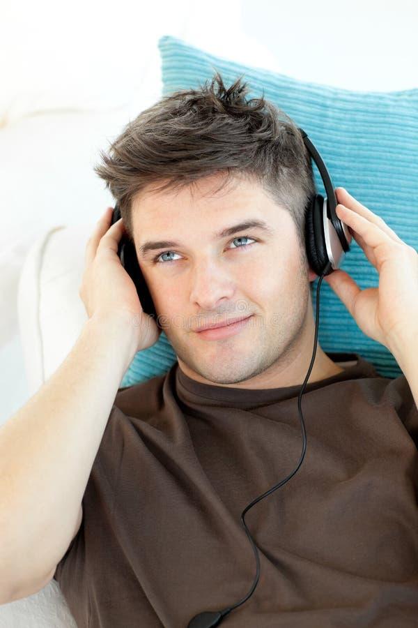 Lächelnder Mann mit Kopfhörern hörend Musik stockbilder