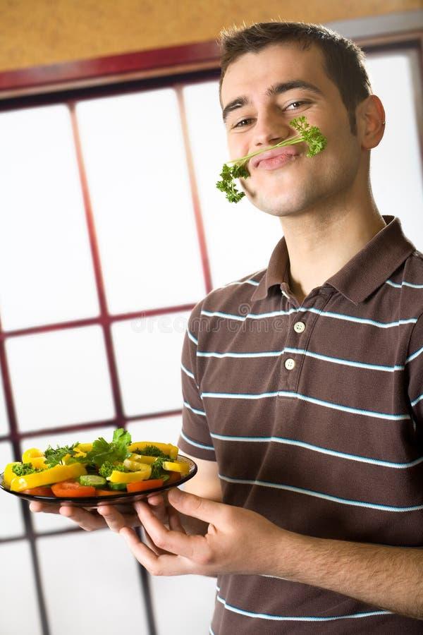Lächelnder Mann mit Salatplatte stockfotos
