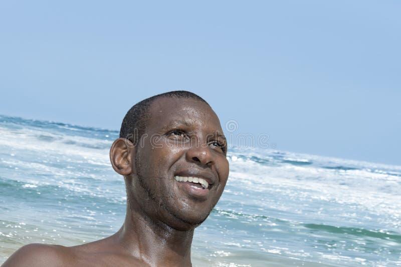 Lächelnder Mann nahe dem rasenden Atlantik, Malika-Strand, Senegal stockfotos