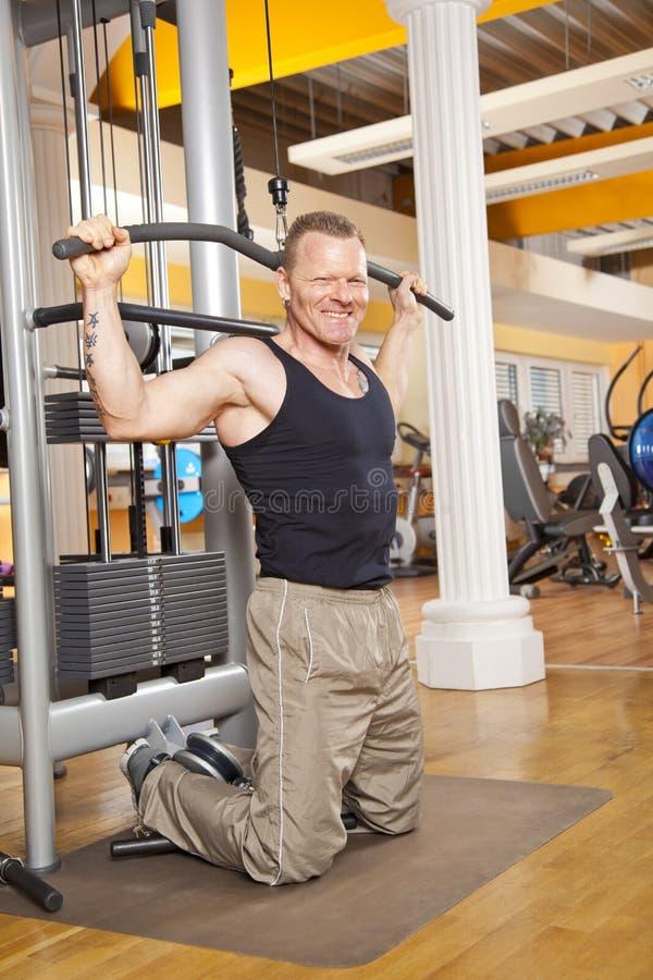 Lächelnder Mann in seinen Vierzigern trainierend in der Gymnastik lizenzfreies stockfoto
