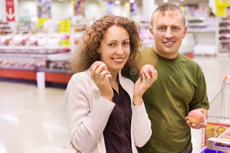 Lächelnder Mann und Frau kaufen Pfirsiche im Supermarkt stockfotos