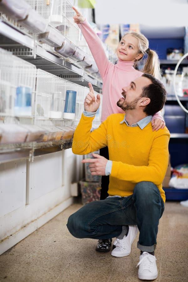 Lächelnder Mann und Tochter, die auf bestem Vogel entscheiden lizenzfreies stockbild