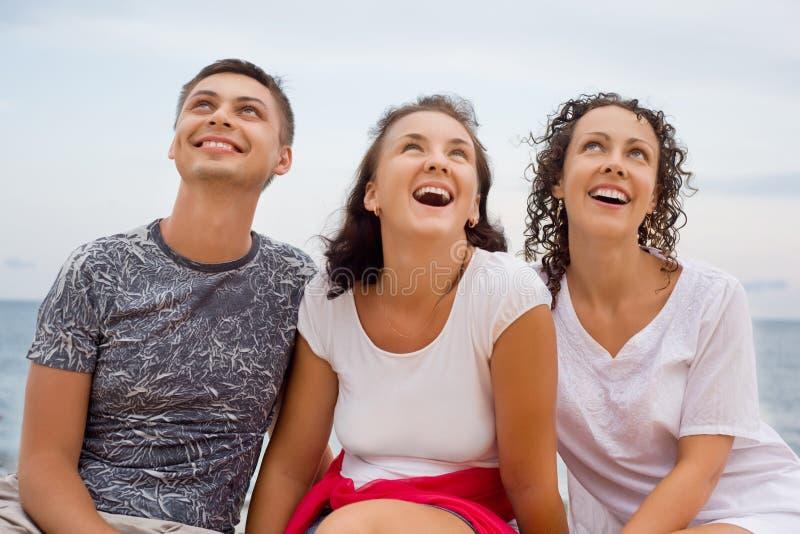 Lächelnder Mann und zwei junge Frauen, die auf Strand sitzen stockfotografie