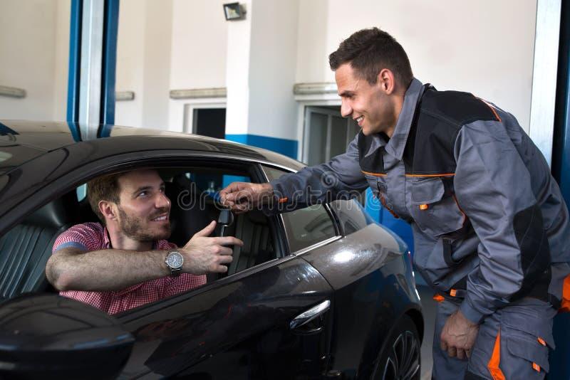 Lächelnder Mechaniker bringt den Schlüssel zu erfülltem Kunden zurück lizenzfreies stockbild