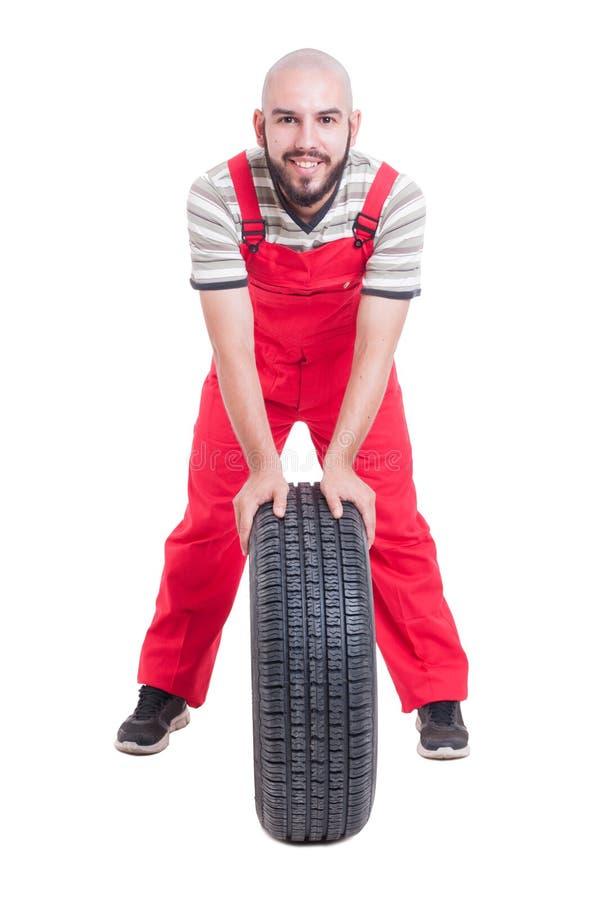 Lächelnder Mechaniker, der auf einem Neuwagenrad stillsteht stockbilder
