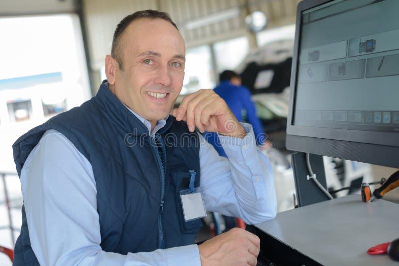 Lächelnder Mechaniker, der Computer an der Reparaturgarage verwendet lizenzfreie stockfotos