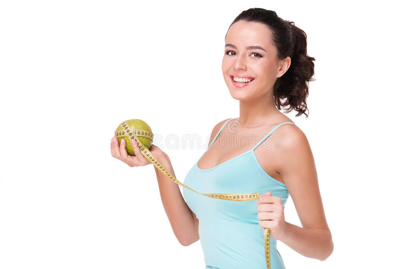 Lächelnder messender Apfel der geeigneten Frau lizenzfreie stockfotos