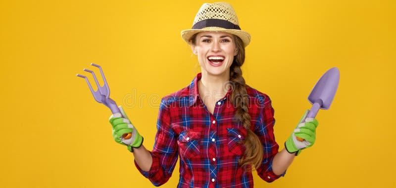 Lächelnder moderner Frauenlandwirt, der Gartenarbeitwerkzeuge zeigt stockfoto