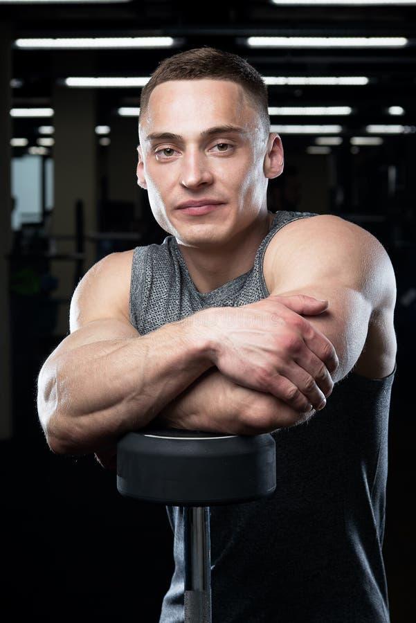 Lächelnder muskulöser Mann mit den großen Armen wirft im grauen Hemd auf stockfotos