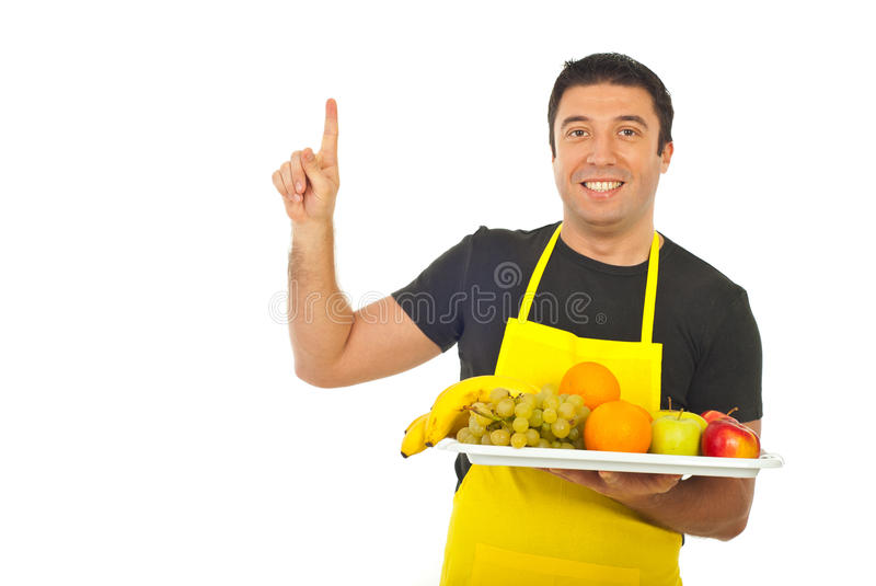 Lächelnder Obsthändler, der aufwärts zeigt stockbilder