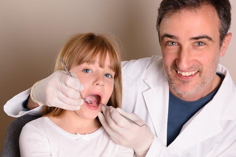 Lächelnder pädiatrischer Zahnarzt, der den Mund eines Mädchens überprüft lizenzfreie stockbilder