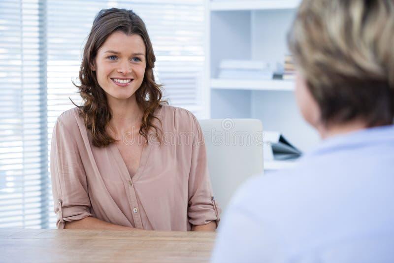 Lächelnder Patient, der einen Doktor konsultiert lizenzfreie stockfotos