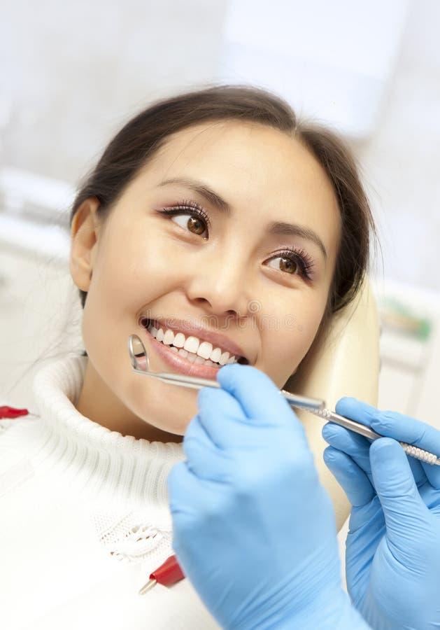 Lächelnder Patient während Zahnarzt, der es überprüft stockfoto