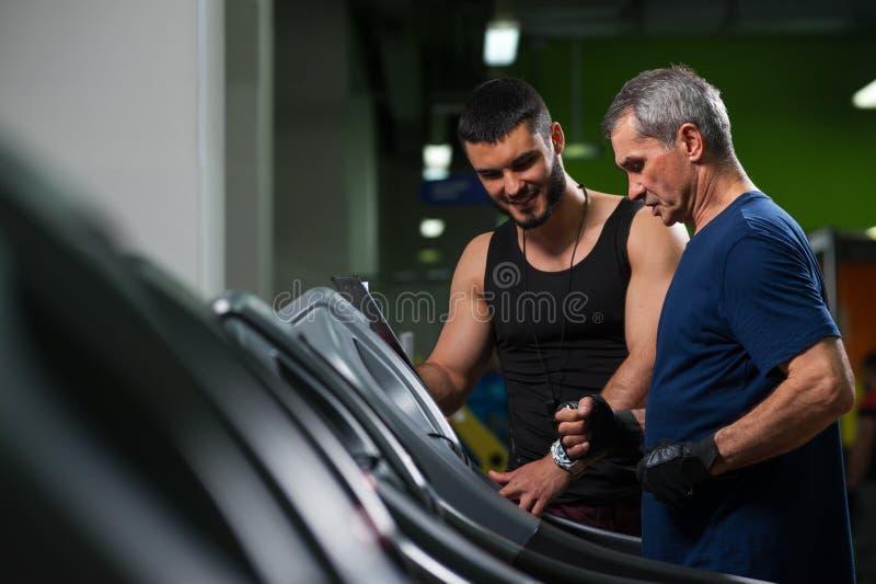 Lächelnder persönlicher Trainer, der mit älterem Mann arbeitet lizenzfreies stockbild