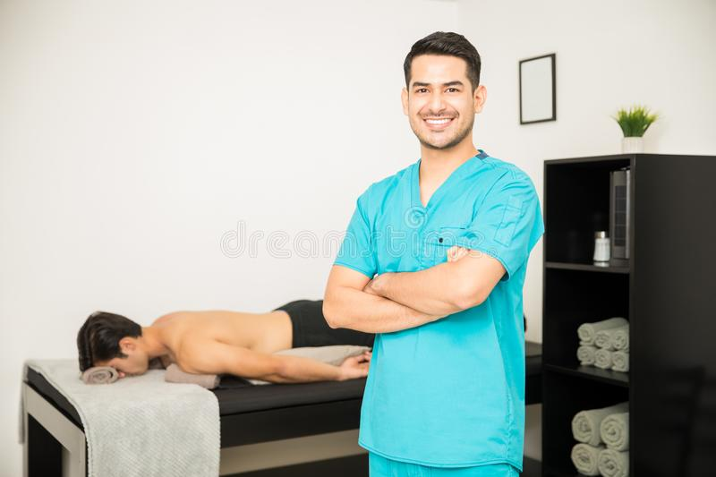 Lächelnder Physiotherapeut Standing Arms Crossed mit Patienten im Ba stockfoto