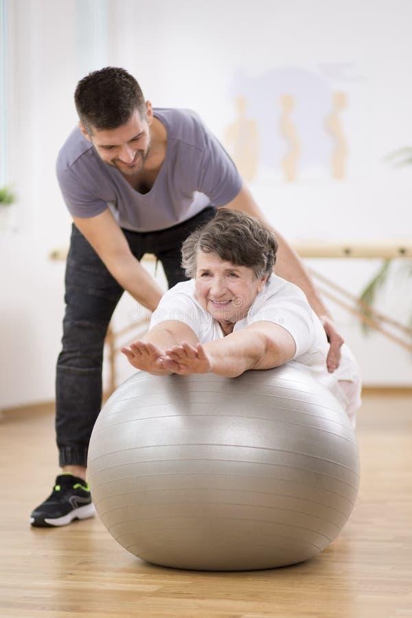 Lächelnder Physiotherapiestudent, welche älterer Frau hilft, auf den trainierenden Ball während der Rehabilitation zu legen lizenzfreies stockbild
