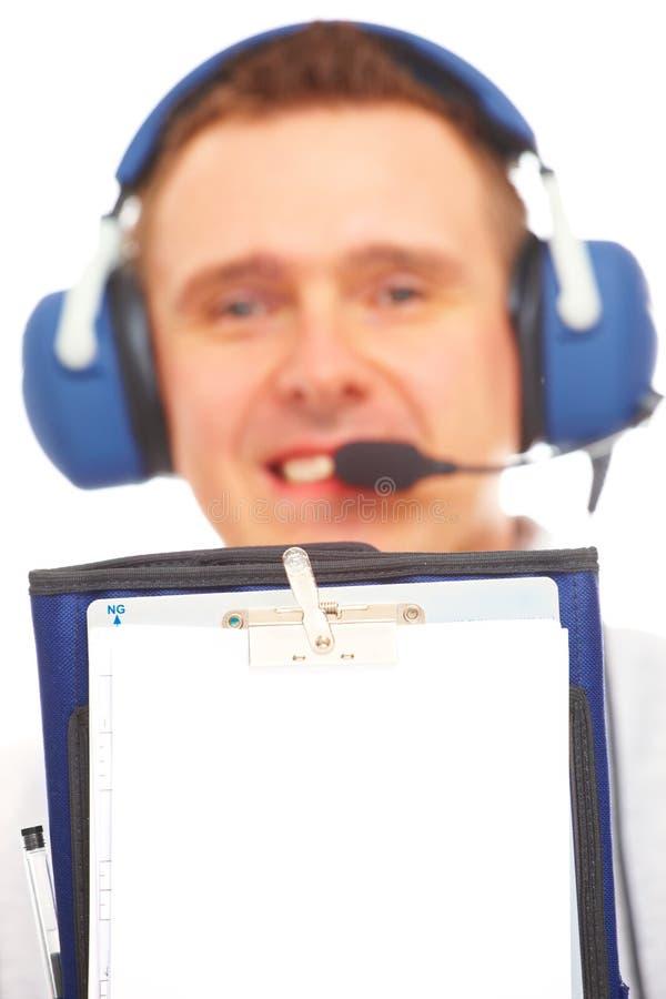 Lächelnder Pilot, der Kneepad zeigt lizenzfreie stockfotografie