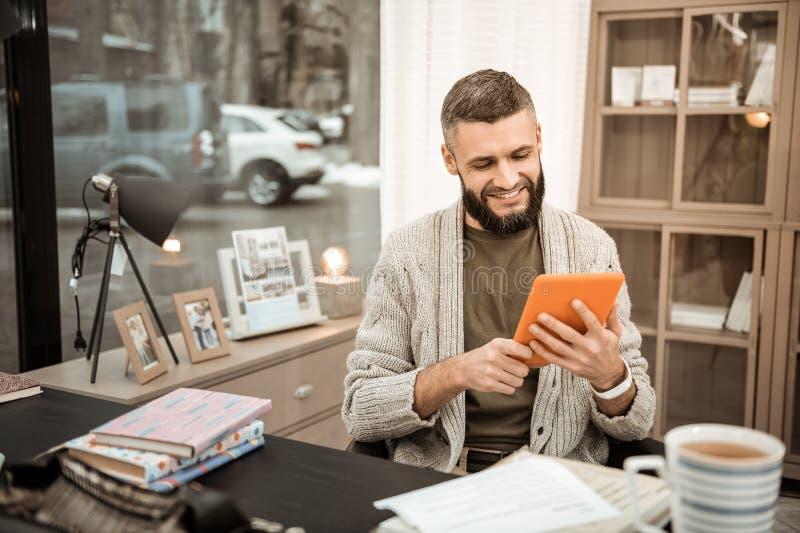 Lächelnder positiver Kerl mit üppigem Bart, Informationen über Smartphone beobachtend stockbilder