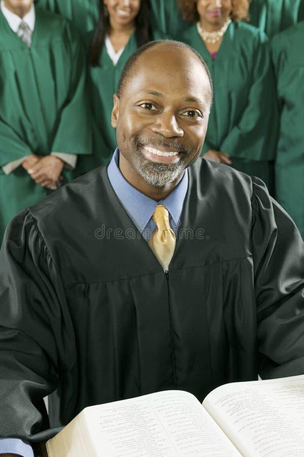 Lächelnder Prediger mit Bibel in der Kirche stockfotografie