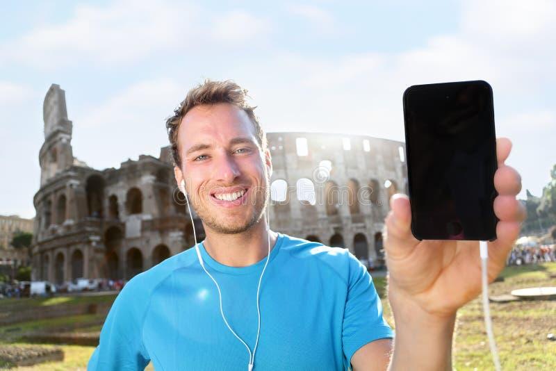 Lächelnder Rüttler, der Smartphone gegen Colosseum zeigt stockfotografie