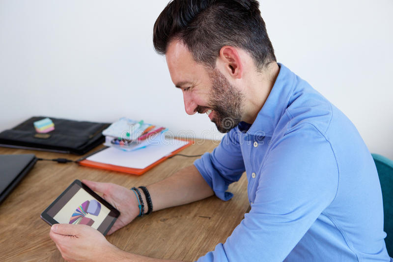 Lächelnder reifer Geschäftsmann, der digitale Tablette am Schreibtisch verwendet stockfotografie