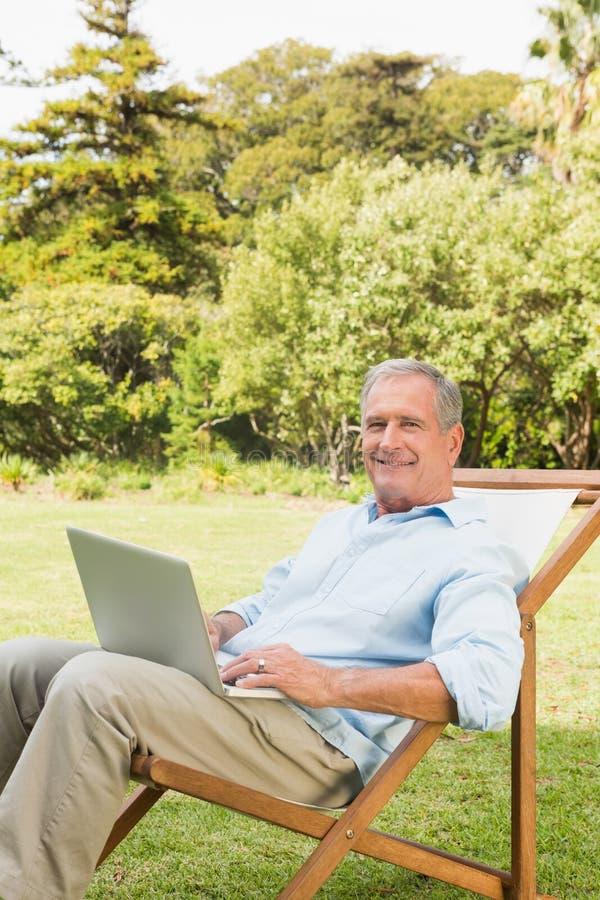 Lächelnder reifer Mann, der Laptop verwendet stockfotos