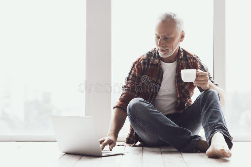 Lächelnder reifer Mann mit Bart unter Verwendung des Laptops zu Hause stockfotografie