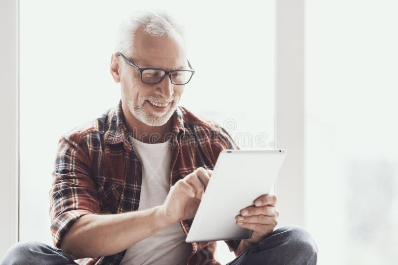 Lächelnder reifer Mann mit Bart unter Verwendung des Tablets zu Hause stockfotografie