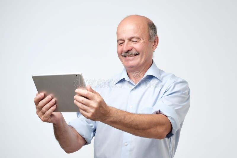 Lächelnder reifer Mann unter Verwendung der digitalen Tablette gegen grauen Hintergrund Entdeckungsbenötigte informationen im Net lizenzfreies stockfoto
