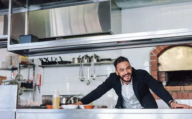 Lächelnder Restaurantbesitzer, der an der Küchenarbeitsplatte steht lizenzfreies stockbild