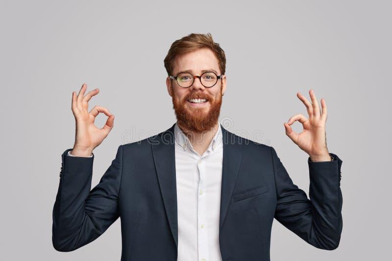 Lächelnder roter bärtiger Geschäftsmann, der O.K. gestikuliert lizenzfreie stockfotos