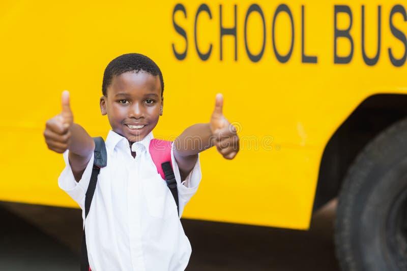 Lächelnder Schüler, der Daumen oben vor Schulbus zeigt stockbild