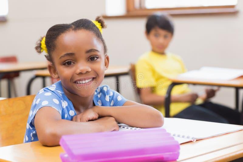 Lächelnder Schüler, der an ihrem Schreibtisch sitzt lizenzfreies stockbild