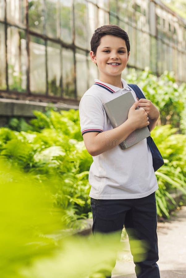 lächelnder Schüler mit dem Rucksack und Buch, die Kamera betrachten lizenzfreie stockfotografie