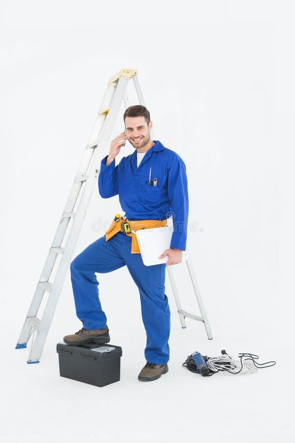 Lächelnder Schlosser mit Werkzeugkasten und Leiter unter Verwendung des Mobiltelefons lizenzfreie stockfotos