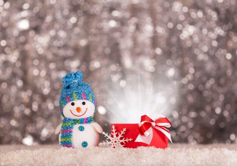 Lächelnder Schneemann und magisches Geschenk im Schnee auf hellem grauem Hintergrund lizenzfreie stockfotos
