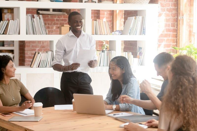 Lächelnder schwarzer Führer, der den Papierbericht lacht mit verschiedenem Team hält stockbild