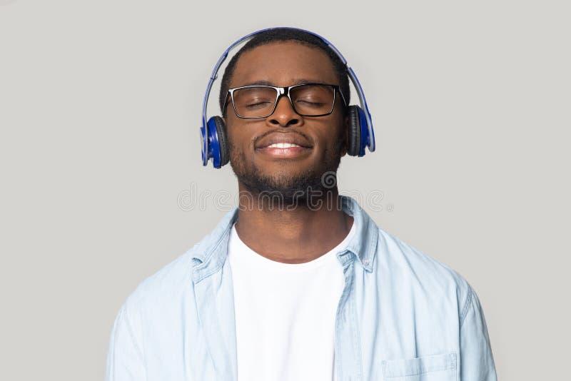 Lächelnder schwarzer Mann in den Gläsern genießen Musik in Bluetooth-Kopfhörern stockbild