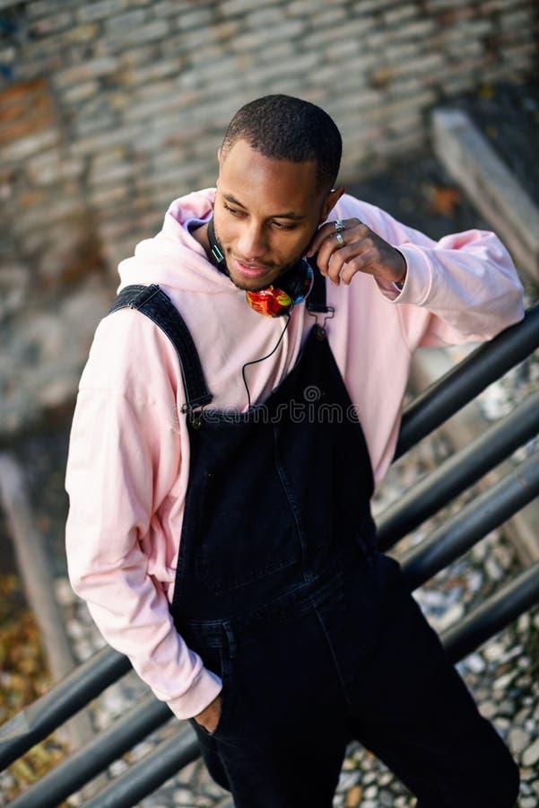 Lächelnder schwarzer Mann, der draußen zufällige Kleidung trägt stockfoto