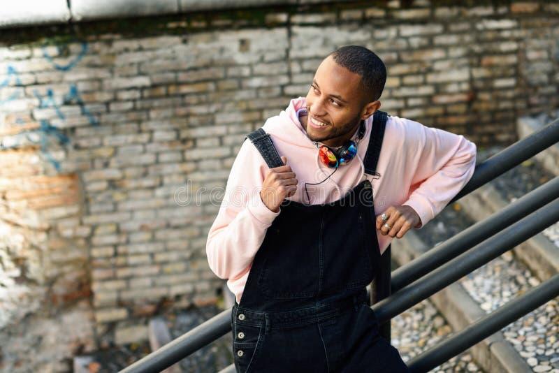 Lächelnder schwarzer Mann, der draußen zufällige Kleidung trägt stockfotografie