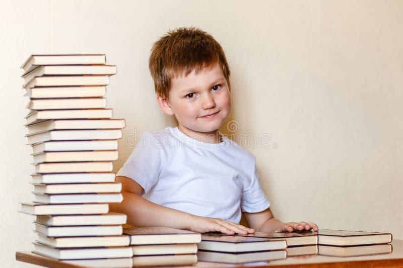 Lächelnder sechsjähriger Junge in einem weißen T-Shirt und in vielen Büchern Erster Sortierer lizenzfreie stockfotos