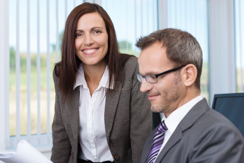 Lächelnder Sekretär mit ihrem Chef stockfotos