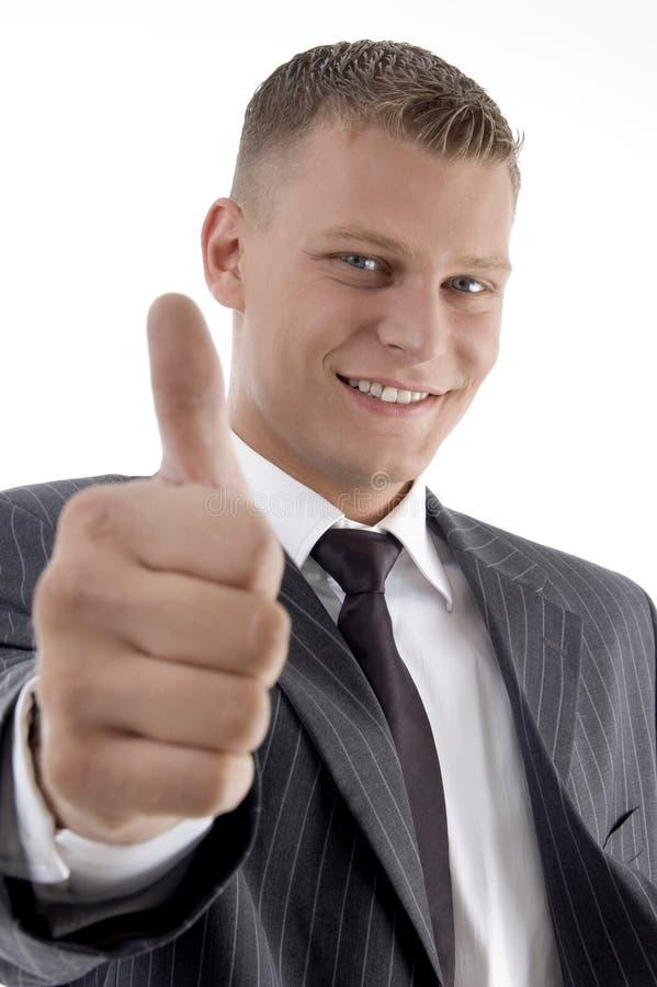 Lächelnder stattlicher junger Manager, der sich Daumen zeigt stockfoto