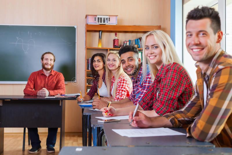 Lächelnder Student Highschool Group schreiben den Test, der Kamera-Professor betrachtet stockfotografie
