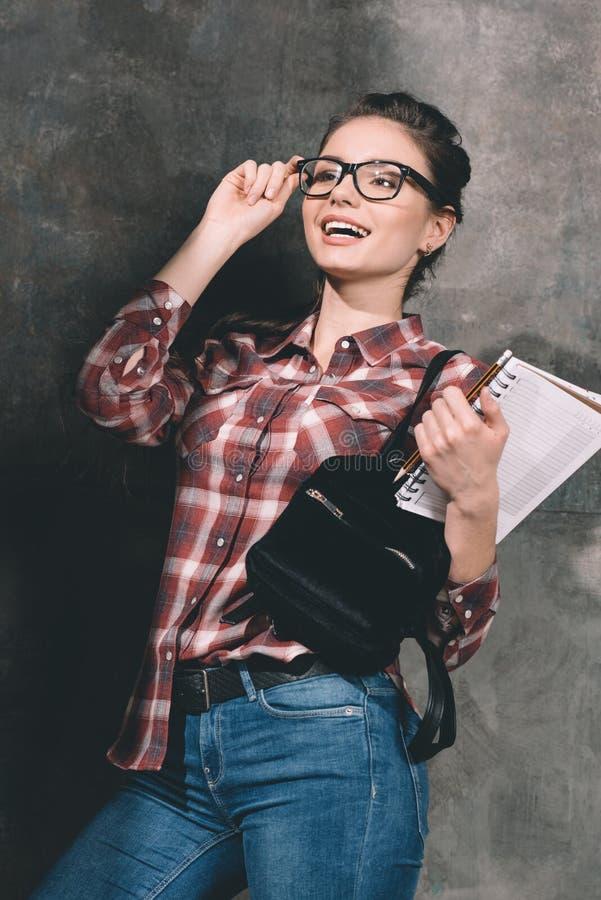 Lächelnder Student mit dem Schreibheft, das an der Wand steht lizenzfreies stockbild