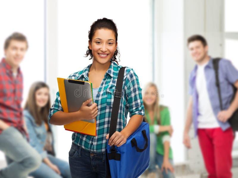 Lächelnder Student mit Ordnern, Tabletten-PC und Tasche stockfoto