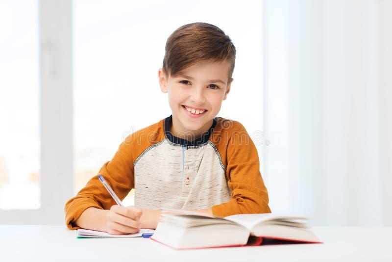 Lächelnder Studentenjunge, der zu Hause zum Notizbuch schreibt lizenzfreies stockfoto
