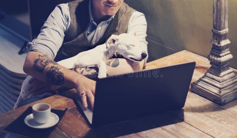 Lächelnder tätowierter Mann in den Brillen, die zu Hause an Laptop beim Sitzen am Holztisch mit dem netten Hund an schläft arbeit stockfotografie