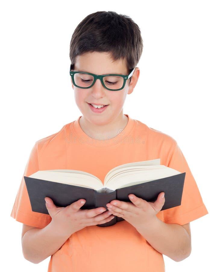 Lächelnder Teenager von dreizehn ein Buch lesend stockfotografie
